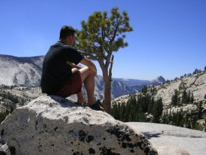 Fabio, sitting on a glacial erratic,  looking out at Yosemite Valley near TIoga road